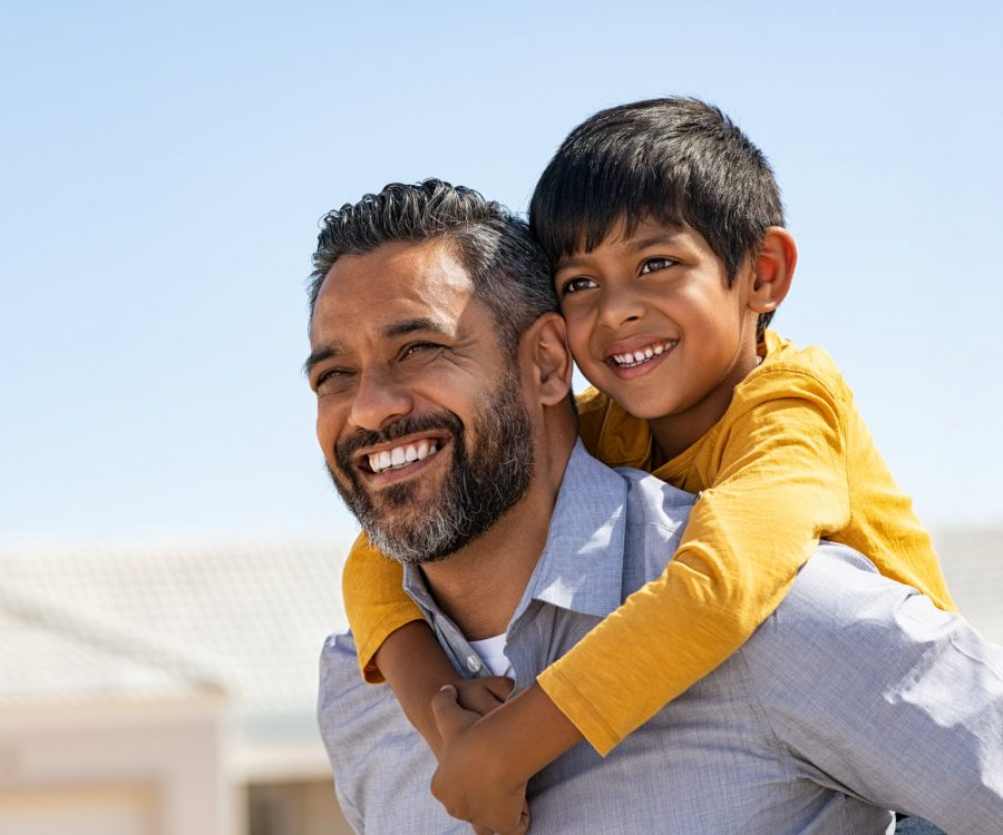 Happy middle eastern child enjoying ride on father back outdoor. Smiling young dad giving piggyback ride to son on street while looking away with copy space. Latin cheerful man carrying on shoulder indian kid: future and vision concept .